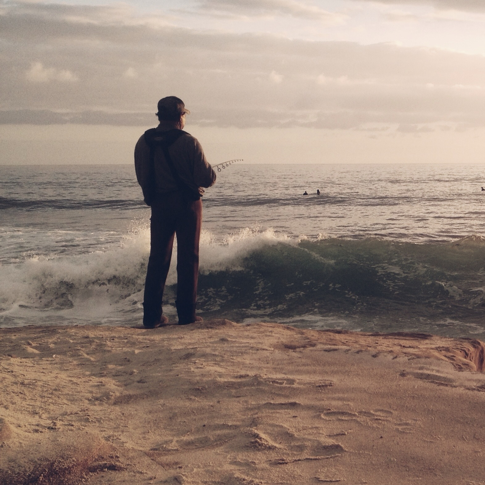 Man stood on the shoreline, facing the sea